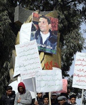 متظاهرون تجمعوا حول صورة لمحمد البوعزيزي في سيدي بوزيد في 0 كانون الثاني/يناير 2011 (ارشيف اف ب, فريد دوفور)